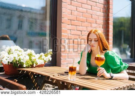Sad Thoughtful Young Woman Drinking Cocktail Through Straw Sitting At Table In Outdoor Cafe In Sunny