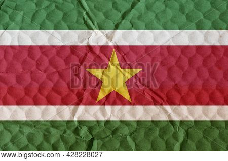Flag Of The Republic Of Suriname On An Uneven Textured Surface. The National Flag Of The Country Is