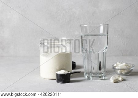 Collagen Powder In A Jar And Measuring Spoon, Collagen Capsules And A Glass Of Water On A Light Gray
