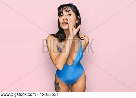 Young hispanic woman wearing swimsuit and sunglasses hand on mouth telling secret rumor, whispering malicious talk conversation