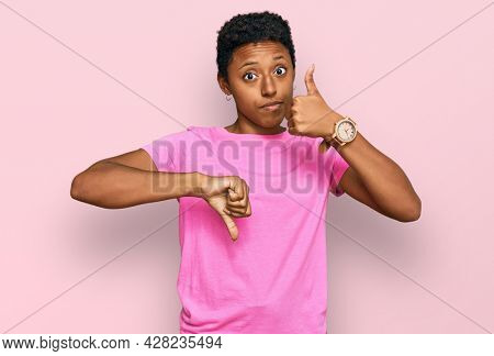 Young african american woman wearing casual clothes doing thumbs up and down, disagreement and agreement expression. crazy conflict