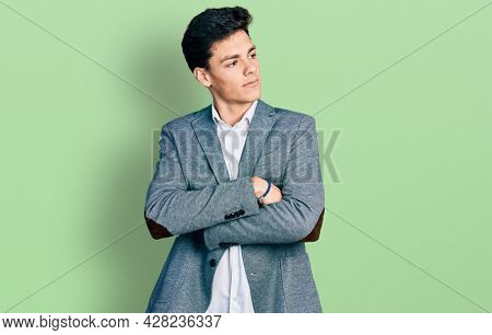 Young hispanic man wearing business clothes looking to the side with arms crossed convinced and confident
