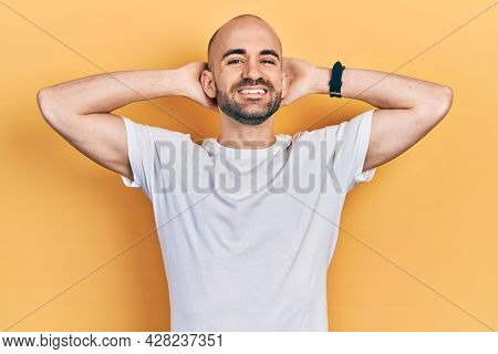 Young bald man wearing casual white t shirt relaxing and stretching, arms and hands behind head and neck smiling happy