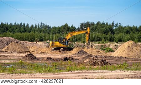 An Industrial Yellow Excavator Develops In A Sandpit Quarry. Industry, Technology, Mining. Heavy Ind