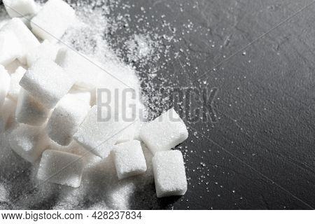Sugar Lumps Piled Up Together Against A Black Background