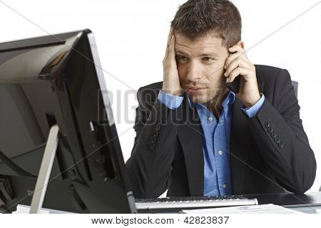 Young businessman looking at screen desperate, talking on mobilephone.