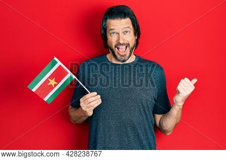 Middle age caucasian man holding suriname flag pointing thumb up to the side smiling happy with open mouth