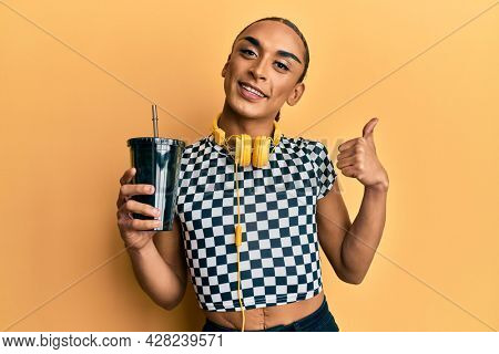 Hispanic man wearing make up and long hair wearing headphones and drinking take away soda smiling happy and positive, thumb up doing excellent and approval sign
