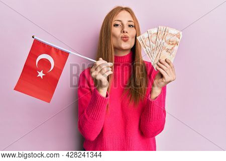 Young irish woman holding turkey flag and liras banknotes looking at the camera blowing a kiss being lovely and sexy. love expression.