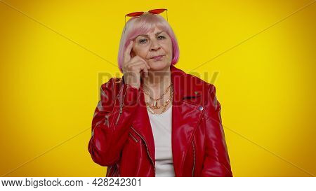Thoughtful Clever Senior Rocker Woman Rubbing Her Chin And Looking Aside With Pensive Expression, Po