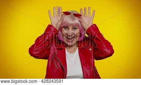 I Am Little Bunny Rabbit. Funny Mature Old Granny Woman Smiling Friendly And Doing Bunny Ears Gestur
