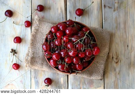 Ripe Juicy Cherries In A Bowl On A Wooden Surface. Organic Cherry Harvest.