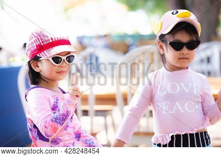 Portrait Two Cute Asian Girls Wearing Sunglasses Preparing To Play On The Beach. Children Wear Hot S