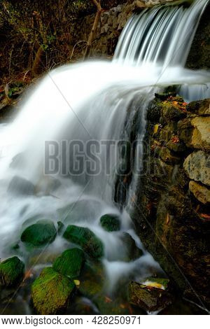 Waterfall of flowing water from stream or creek with fall autumn leaves
