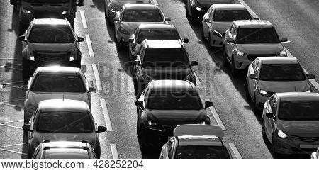Cars On A City Road Are In A Traffic Jam At Rush Hour On A Sunny Summer Evening