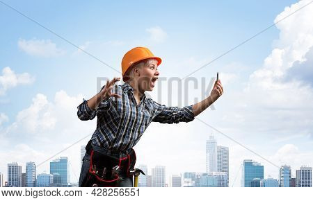 Expressive Blonde Woman In Workwear And Hardhat Shouting Into Smartphone. Portrait Of Young Emotiona