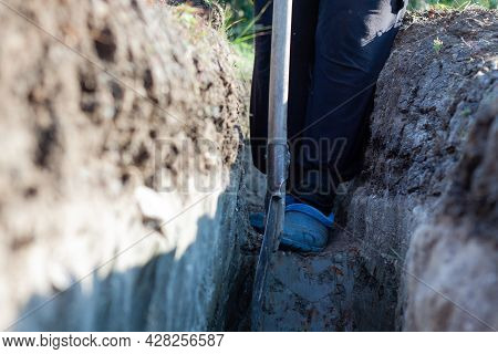 Photo Of A Woman Digging A Ditch In The Ground From Her House To Drain Water. Woman Working With A S