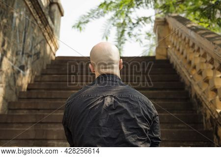 Back View Of A Bald Beefy Caucasian Man Standing In Front Of The Stairs. Unidentified Incognito Pers