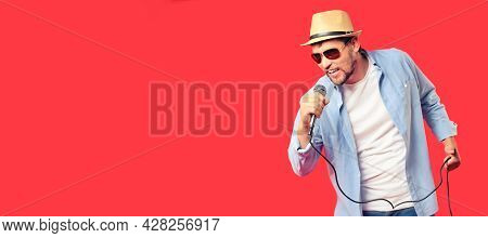A Caucasian Man In A Hat And Sunglasses Sings A Song Into The Microphone. Vocal Performance Of The S