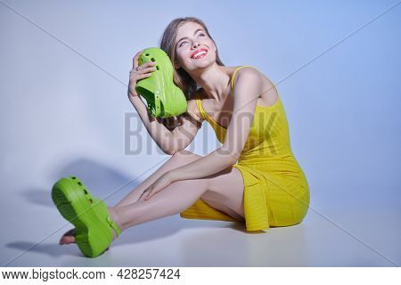 Full length portrait of a beautiful blonde girl  in bright clothing sitting on the floor in light green sabot. Fashion studio shot with copy space.