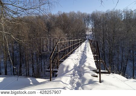 The Landscape With Bridge Through Ravine In Wood. Nature At Winter Length Of Time On Background Blue