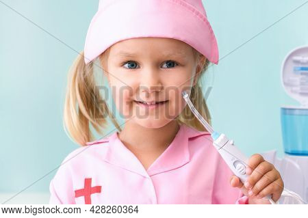 Little Girl In A Nurses Gown Brushes Her Teeth Using An Irrigator. Girl Is Brushing Her Teeth With A