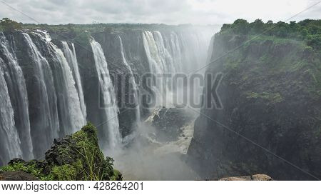 The Streams Of Victoria Falls Rush Into The Abyss. At The Bottom Of The Gorge Flows A Stormy River W