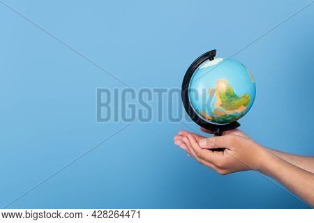 Cropped View Of Schoolkid Holding Globe On Hands Isolated On Blue