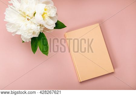 Closed Notebook For Writing Dreams And Ideas And Big White Peony Flowers Laying On Pink Background.