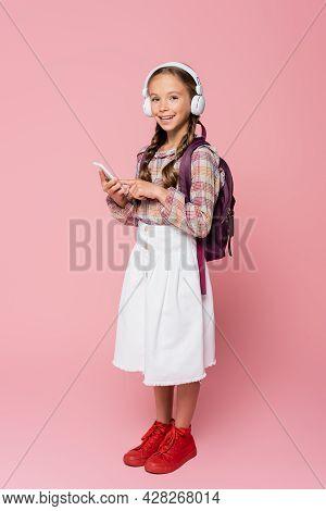 Preteen Schoolkid In Headphones Holding Smartphone On Pink Background