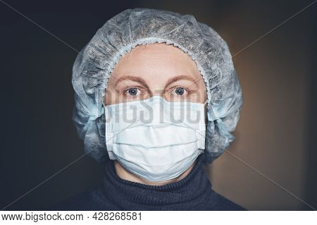 Portrait Of Mature Woman In Protective Mask And Medical Cap.