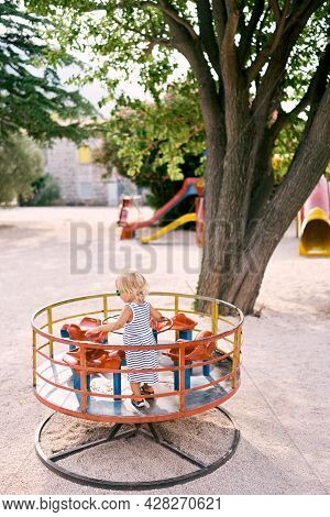 Little Girl In Sunglasses Stands On A Turntable Swing. Back View