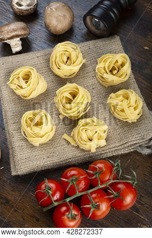 Raw Pasta Tagliatelle With Fresh Tomatoes, Peppers, Asparagus Beans, Spices And Cheese On A Wood Tab