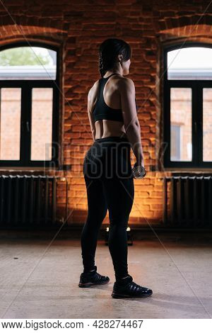 Rear View Of Young Athletic Woman With Beautiful Strong Body Wearing Activewear Holding Dumbbells Du