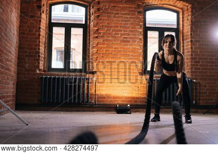 Front View Of Fitness Young Athletic Woman With Strong Beautiful Body In Black Activewear Exercising
