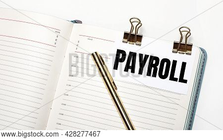 On A Light Background, An Open Notebook, A Sheet Of Paper With Gold Clips And The Text Payroll And A