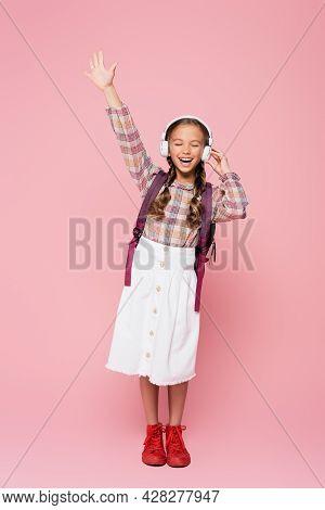 Schoolkid In Headphones Singing On Pink Background