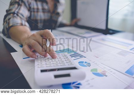 Businessman Or Accountant Is Using A Calculator To Calculate Financial Information From A Folder On