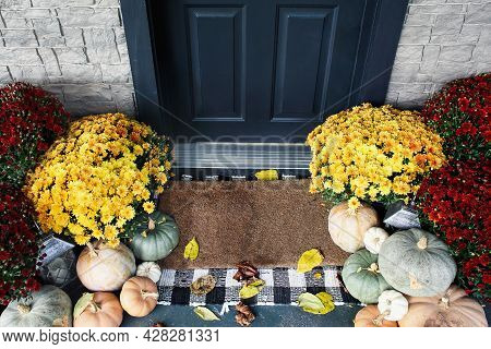 Welcome Door Mat Of Front Porch That Has Been Decorated For Autumn With Heirloom White, Orange And G