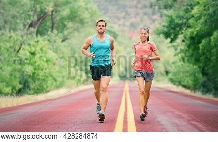 Summer run man and woman runners couple fit people jogging training for marathon. Young athletes on fast cardio jog workout in summer park road.
