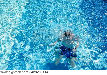 Caucasian Man In Swimming Trunks Under Water Dives In The Pool With Blue Tiles On Vacation. Adult Ma