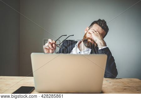 tired businessman touching his eyes bad eyesight, exhaustion