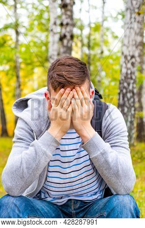 Sad Young Man Close His Face And Sit In The Forest Alone