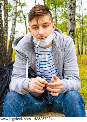 Man In The Flu Mask Smoke A Cigarette In The Autumn Forest
