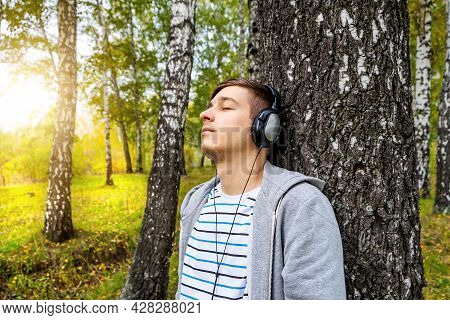 Young Man In Headphones Listen To The Music In The Forest