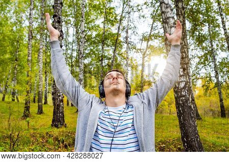 Young Man In Headphones With Hands Up On The Nature Background