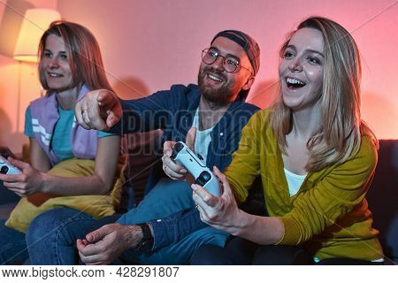 Group Of Friends Playing Video Games At Home And Having Fun. Playful Friends Having Fun While Consol