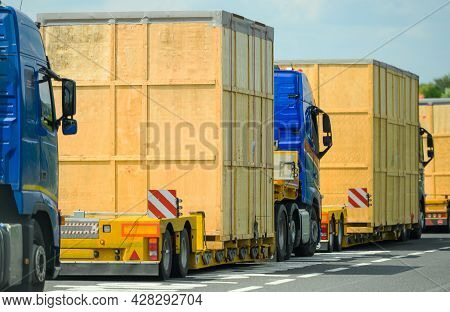 Heavy Oversize Load Convoy On The Route To Destination. Few Semi Trucks Pulling Large Wooden Oversiz