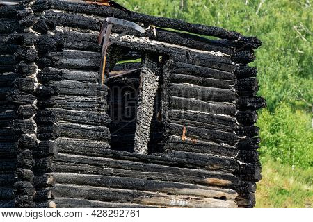 Remains Of A Burnt House Against The Backdrop Of A Green Forest. The Charred Black Ruins Of A Wooden