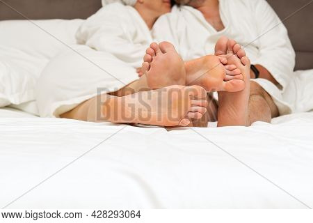 Lovers Feet Of A Couple In Love In A Bed With White Linens